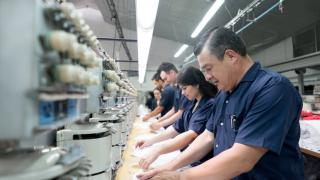 People operating machines at an embroidery factory
