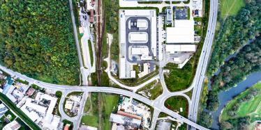 Aerial view of industrial buildings, highway and small town Nova Bana in Slovakia surrounded by green nature.